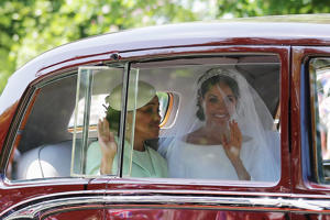 a person driving a car: Meghan Markle and her mother, Doria Ragland, wave to wellwishers as they drive to Windsor Castle for the ceremony.