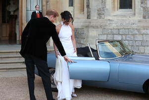 Duke and Duchess of Sussex: Britain's Prince Harry, Duke of Sussex, (L) opens the passenger door of an E-Type Jaguar car for his wife Meghan Markle, Duchess of Sussex, (R) as they leave Windsor Castle in Windsor on May 19, 2018 after their wedding to attend an evening reception at Frogmore House. (Photo by Steve Parsons / POOL / AFP) (Photo credit should read STEVE PARSONS/AFP/Getty Images)