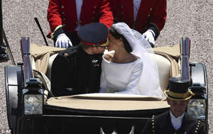 a man wearing a hat: Mok captured Prince Harry and Meghan exchanging a tender kiss during the carriage ride