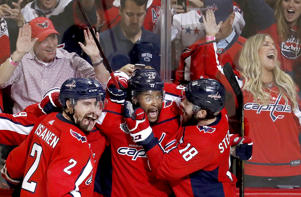 Washington Capitals forward Devante Smith-Pelly, center, celebrates his goal against the Vegas Golden Knights with Matt Niskanen, left, and Chandler Stephenson, during the third period in Game 3 of the NHL hockey Stanley Cup Final, Saturday, June 2, 2018, in Washington.