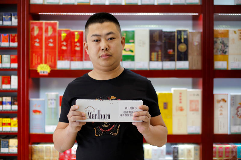 "Shan Yuliang, salesperson at a cigarette and wine shop, poses with a carton of Marlboro cigarettes in Beijing, China, April 8, 2018. ""The moment I saw the news about the trade war on the internet, I felt something big was coming. Previously I would not think about what brand to buy. Now I will give it a second thought and avoid buying American products to defend my country,"" Shan said."