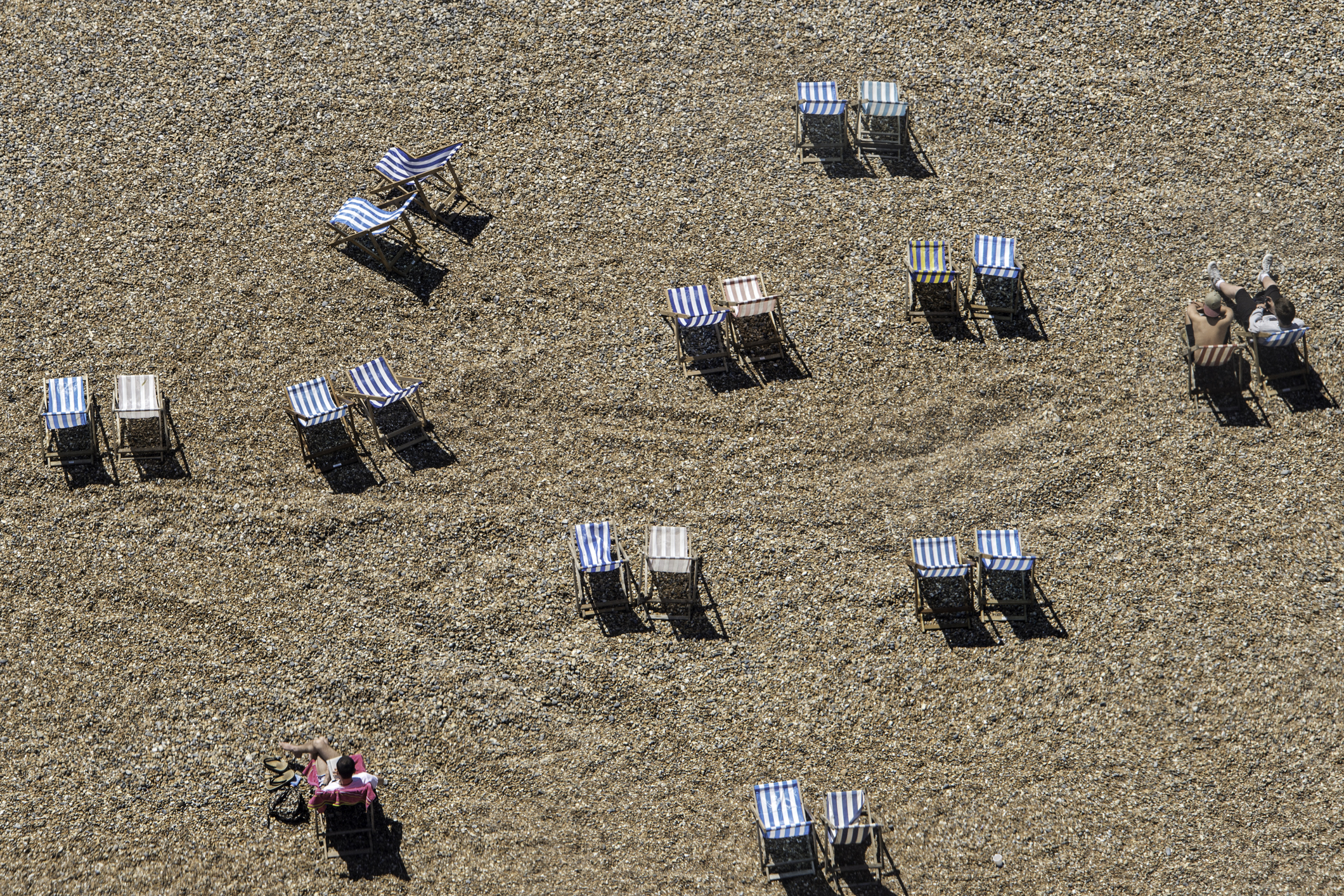 Slide 4 of 39: Looking down on a number of deck chairs some occupied some empty on Brighton beach on a sunny summers day.