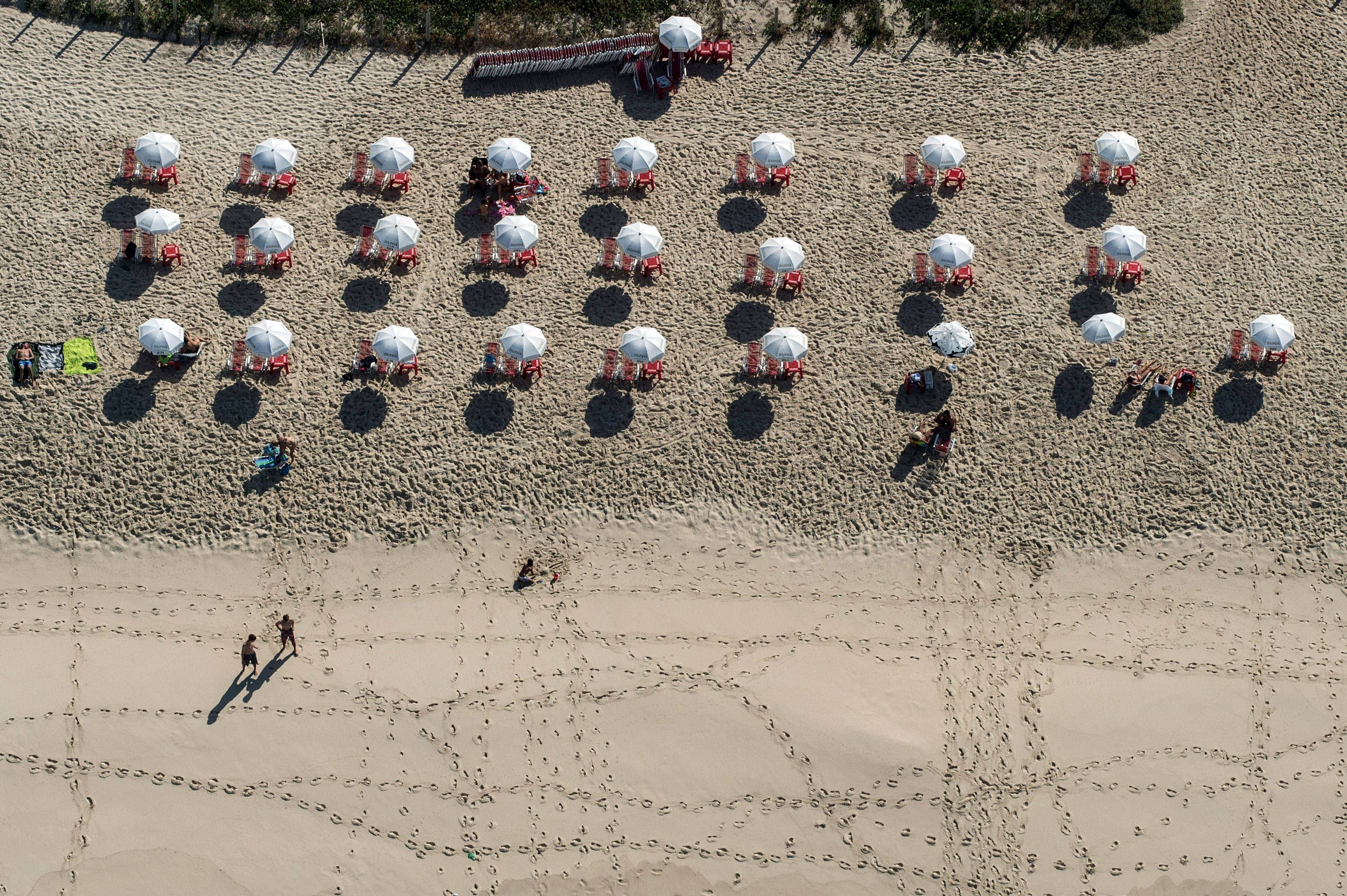 Slide 23 of 39: Aerial view of the beach at Barra da Tijuca in Rio de Janeiro, Brazil, on June 28, 2014. AFP PHOTO / YASUYOSHI CHIBA        (Photo credit should read YASUYOSHI CHIBA/AFP/Getty Images)