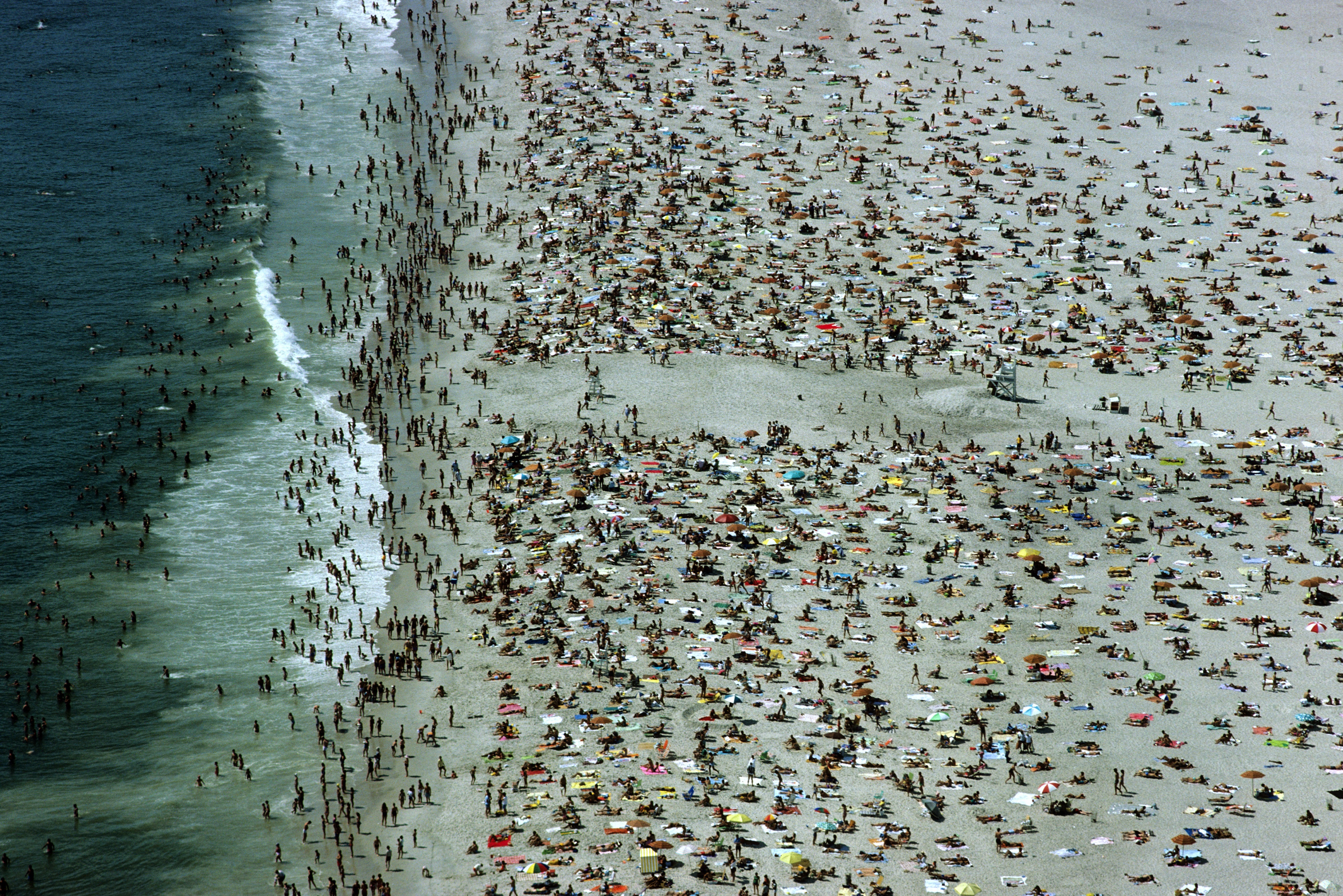 Slide 28 of 39: Aerial view of sunbathers and swimmers enjoying a summer day at the beach. (Photo by ANDREW HOLBROOKE/Corbis via Getty Images)