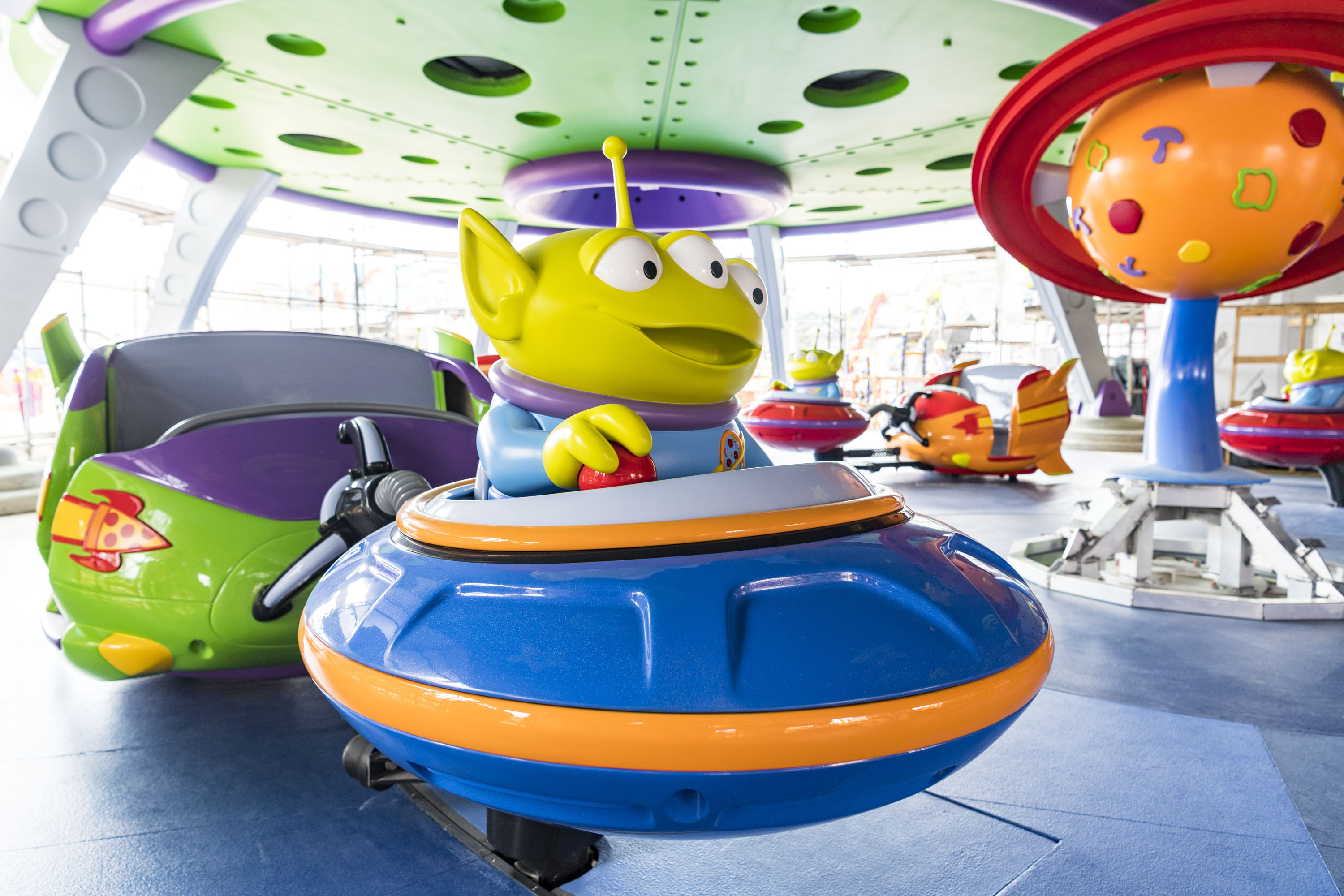 """Slide 3 of 15: Little green aliens from the hit Disney●Pixar """"Toy Story"""" films pilot toy rocket ships in the Alien Swirling Saucers attraction that will be part of the new Toy Story Land opening June 30, 2018, at Disney's Hollywood Studios. The out-of-this-world attraction is inspired by Andy's toy play set from the Pizza Planet restaurant. With multi-colored lighting and sound effects from throughout the galaxies, Walt Disney World guests will swirl and whirl in the toy rocket ships while the aliens try to get captured by """"The Claw"""" that hangs overhead. (Matt Stroshane, photographer)"""