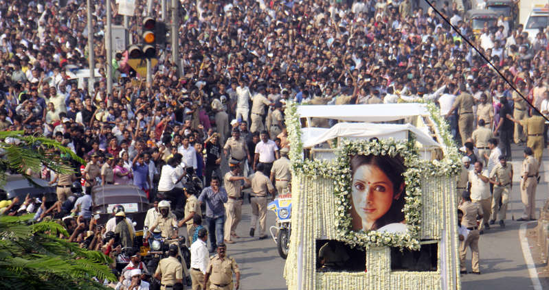 Fans watch as the funeral cortege of the late Bollywood actress Sridevi Kapoor passes through at Vile Parle on February 28, 2018 in Mumbai
