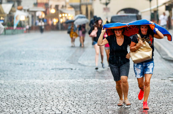 Slide 1 of 38: Women take cover from heavy rain at the Old Town Square in Prague, Czech Republic, Friday, June 1, 2018.