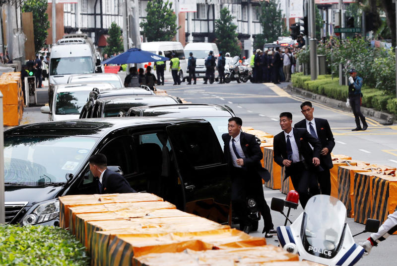 North Korean security personnel run next to a motorcade believed to be carrying North Korea's leader Kim Jong Un in Singapore