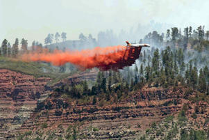 An aircraft makes a fire retardant drop on a wildfire in the hills and forests near Durango, Colo., Friday, June 8. The blaze in southwestern Colorado forced hundreds of evacuations and was expected to reach homes by Friday, authorities said.
