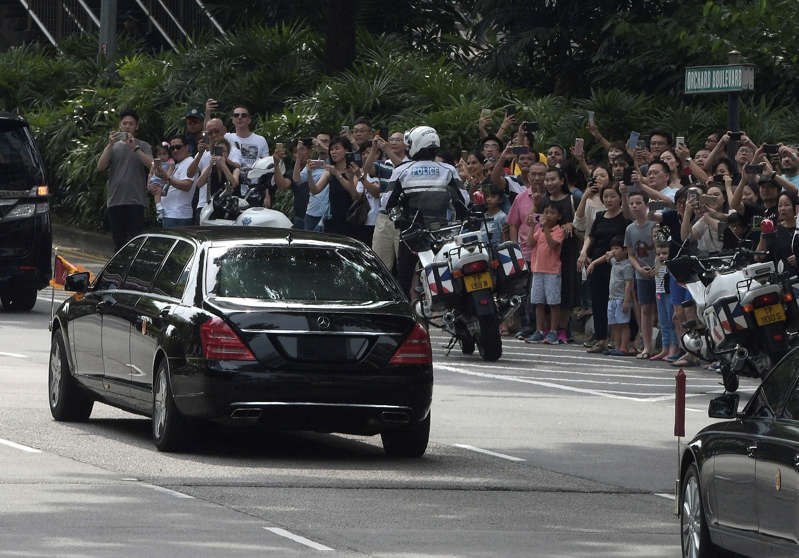 The crowds watch the North Korean motorcade carrying Kim Jong Un