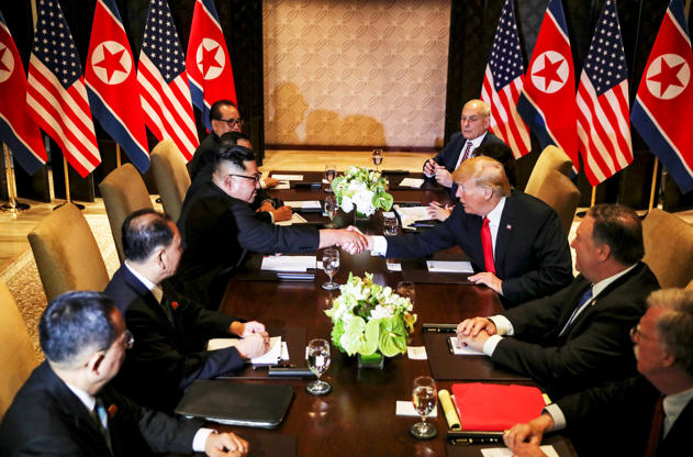 Slide 1 of 51: U.S. President Donald Trump shakes hands with North Korea's leader Kim Jong Un before their expanded bilateral meeting at the Capella Hotel on Sentosa island in Singapore June 12, 2018.