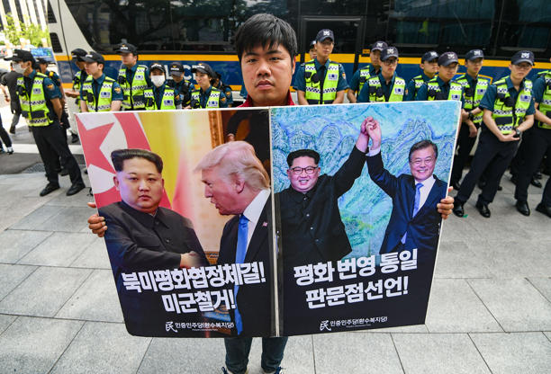 Slide 4 of 51: A south Korean activists holds a placard showing North Korean leader Kim Jong Un, US President Donald Trump and  President Moon Jae-in during a rally demanding a peace treaty between North Korea and the US near the US embassy in Seoul on June 12, 2018. - Donald Trump and Kim Jong Un have become on June 12 the first sitting US and North Korean leaders to meet, shake hands and negotiate to end a decades-old nuclear stand-off.