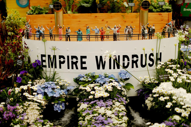 """The """"Windrush Garden"""", conceived by television presenter Floella Benjamin to commemorate the 70th anniversary of the arrival of the Empire Windrush vessel in Britain, is displayed at the RHS (Royal Horticultural Society) Chelsea Flower Show in London, Monday, May 21, 2018. The organizers consider the Chelsea Flower Show the world's most prestigious flower show and celebration of horticultural excellence and innovation. In 1948 the Empire Windrush ship brought hundreds of Caribbean immigrants to a Britain seeking nurses, railway workers and others to help it rebuild after the devastation of World War II. (AP Photo/Matt Dunham)"""