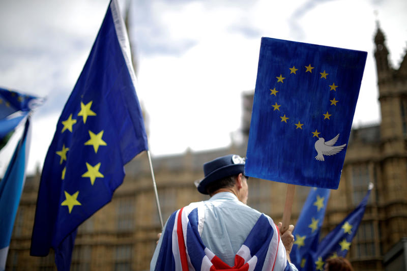 In this photo taken Wednesday, June 20, 2018, an anti-Brexit, pro-EU supporter holds an EU flag and a placard during a protest backdropped by the Houses of Parliament in London. The divisions opened up by the 2016 referendum have not healed, but hardened, splitting Britain into two camps: leavers and remainers. Almost the only thing the two groups share is pessimism about the way Brexit is going. (AP Photo/Matt Dunham)