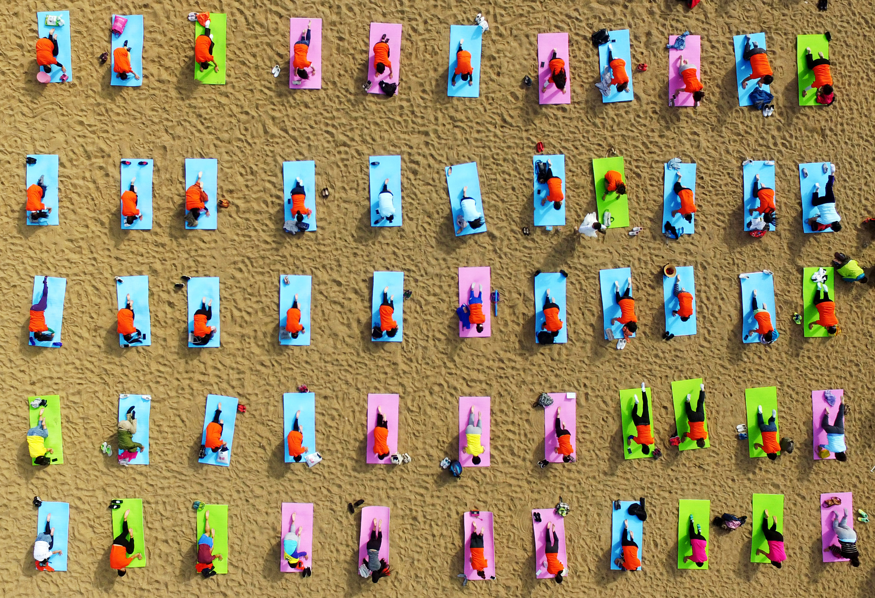 Slide 2 of 39: RIZHAO, CHINA - OCTOBER 06: Aerial view of many people practicing yoga on the beach of Wanpingkou Scenic Spot on October 6, 2016 in Rizhao, Shandong Province of China. Wanpingkou Scenic Spot launched the Sand Beach Cultural Week featuring beach volleyball, beach soccer, sand sculpture and yoga activity during the National Day Holiday. About 300 citizens and tourists signed up for the experience activity of yoga at Wanpingkou Scenic Spot. (Photo by VCG/VCG via Getty Images)