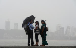 People stand on the sea front during heavy monsoon rain showers in Mumbai