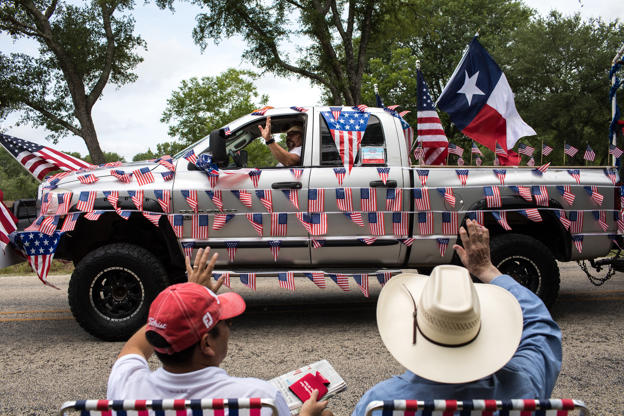 Slide 1 of 26: Spectators wave as a pickup truck covered in American flags drives by during the 168th annual Round Top Fourth of July Parade on July 4, 2018 in Round Top, Texas. The Round Top community's Fourth of July celebration started in 1851 and is known as the longest running Fourth of July celebration west of the Mississippi.