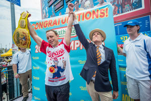 CAPTION: NEW YORK, NY - JULY 04: Joey Chestnut wins the 2018 Nathan's Hot Dog Eating Contest and sets a new record by eating 74 hot dogs in 10 minutes on July 4, 2018 in the Coney Island neighborhood of the Brooklyn borough of New York City.