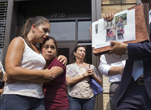 As pictures of children separated from their families are displayed, Yeni Gonzalez, a Guatemalan mother who was separated from her three children at the U.S.-Mexico border, center, is embraced by volunteer Janey Pearl, center left, during a news conference Tuesday, July 3, 2108 in New York.