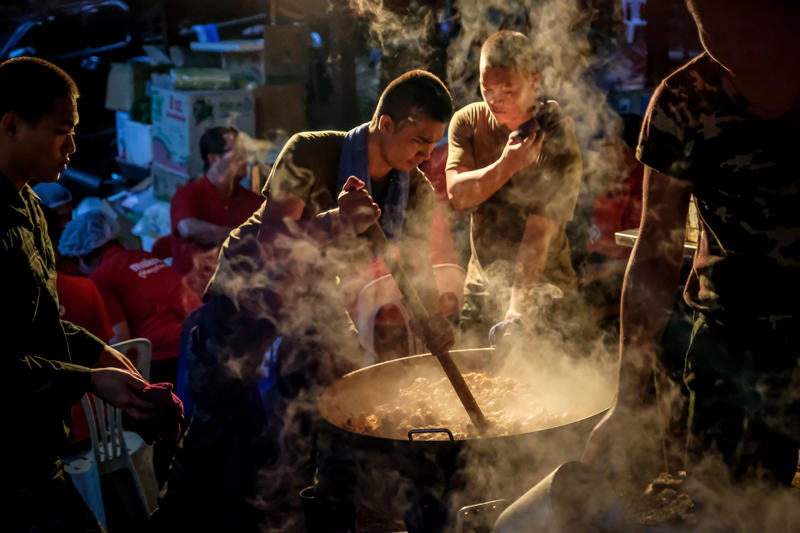 CHIANG RAI, THAILAND - JULY 5: Military personnels cooks dinner for rescuers at the makeshift camp at Khun Nam Nang Non Forest Park to continue the rescue operation on July 05, 2018 in Chiang Rai, Thailand. The 12 boys and their soccer coach have been found alive in the cave here theyve bee missing for over a week after monsoon rains blocked the main entrance in northern Thailand. Videos released by the Thai Navy SEAL shows the boys, aged 11 to 16, and their 15-year-old coach are in good health in Tham Luang Nang Non cave and the challenge now will be to extract the party safely. (Photo by Linh Pham/Getty Images)