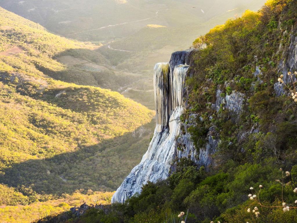 Diapositiva 8 de 51: Aunque de lejos parece una caída de agua, Hierve el Agua es una formación rocosa producto del escurrimiento de agua con alto contenido de minerales y que con el tiempo ha tomado esa forma. El agua tibia que proviene del monte forma una alberca natural en la cima en la que los visitantes pueden bañarse.