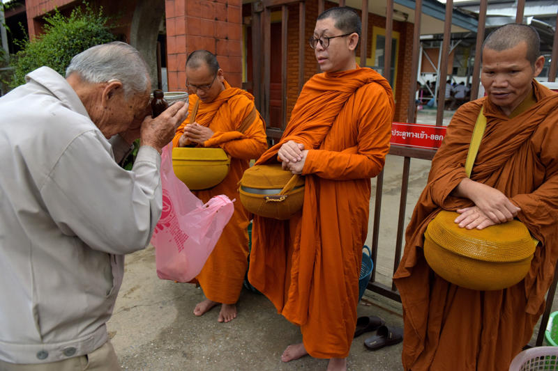 A Thai man prays to Buddhist monks near the hospital where the boys rescued after being trapped in a nearby cave for nearly two weeks have being brought for observation, in the northern Thai city of Chiang Rai on July 9, 2018. - Four boys among the group of 13 trapped in a flooded Thai cave for more than a fortnight were rescued on July 8 after surviving a treacherous escape, raising hopes elite divers would also save the others soon. (Photo by TANG CHHIN Sothy / AFP)        (Photo credit should read TANG CHHIN SOTHY/AFP/Getty Images)