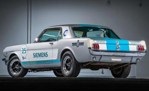 a green and white truck parked next to a car: This Autonomous 1965 Ford Mustang Is Going to Drive Itself in a Hill-Climb