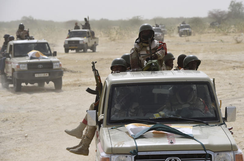 Nigerien army forces patrol in pickup trucks.