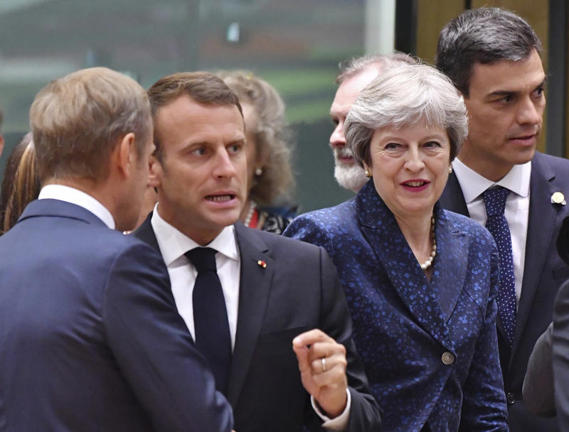 French President Emmanuel Macron, second left, speaks with European Council President Donald Tusk, left, as Spanish Prime Minister Pedro Sanchez, right, and British Prime Minister Theresa May, second right, enter the room during a round table meeting at an EU summit in Brussels, Thursday, June 28, 2018.