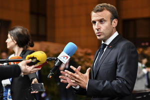 French President Emmanuel Macron talks with journalists as he leaves an EU summit in Brussels, early Friday, June 29, 2018.