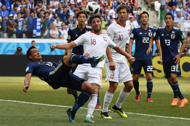 Slide 30 of 100: Japan's defender Tomoaki Makino (L) makes a bycicle kick past Poland's defender Bartosz Bereszynski (18) and Poland's midfielder Grzegorz Krychowiak (10) during the Russia 2018 World Cup Group H football match between Japan and Poland at the Volgograd Arena in Volgograd on June 28, 2018. (Photo by Mark RALSTON / AFP) / RESTRICTED TO EDITORIAL USE - NO MOBILE PUSH ALERTS/DOWNLOADS        (Photo credit should read MARK RALSTON/AFP/Getty Images)