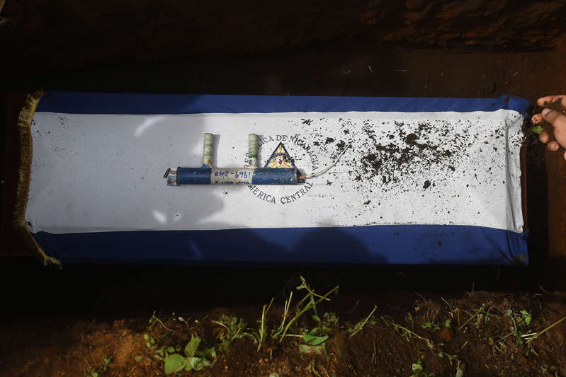 A homemade mortar lies over the coffin of Marvin Lopez, 49, who was shot in the throat during clashes with riot police and members of the Sandinista youth, during his funeral in Masaya, about 35 km from Managua on June 20, 2018. - Residents in the Nicaraguan opposition bastion of Masaya were on Wednesday holding off an offensive by police and pro-government paramilitaries as fresh violence flared across the Central American country. Funerals were held for three people killed in clashes in the flashpoint city on Tuesday, bringing to 187 the number of dead since protests against President Daniel Ortega's government began on April 18. (Photo by Marvin RECINOS / AFP)        (Photo credit should read MARVIN RECINOS/AFP/Getty Images)