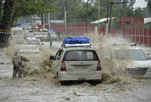 Vehicles drive along a flooded road after a heavy rainfall in Srinagar on June 30, 2018