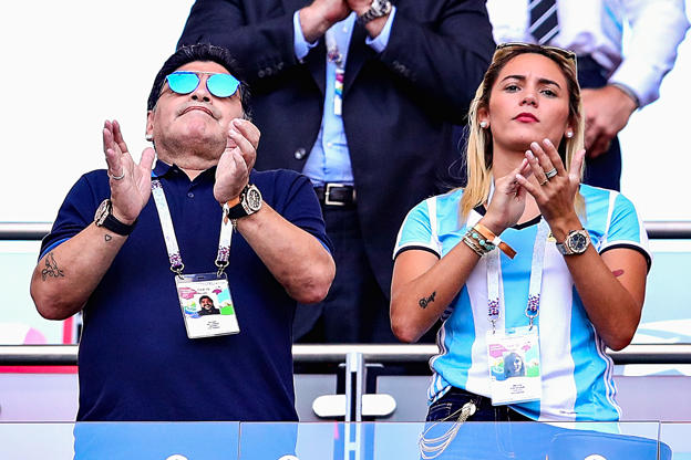Slide 13 of 75: KAZAN, RUSSIA - JUNE 30:  Former Argentina player and manager Diego Maradona looks on with girlfriend Rocio Oliva from the crowd during the 2018 FIFA World Cup Russia Round of 16 match between France and Argentina at Kazan Arena on June 30, 2018 in Kazan, Russia.