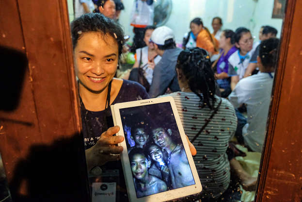 Slide 1 de 111: CHIANG RAI, THAILAND - JULY 2: Relatives of the missing boys show photos of them after the 12 boys and their soccer coach have been found alive in the cave where they've been missing for over a week after monsoon rains blocked the main entrance on July 02, 2018 in Chiang Rai, Thailand. Chiang Rai governor Narongsak Osatanakorn announced on Monday that the boys, aged 11 to 16, and their 25-year-old coach were being rescued from Tham Luang Nang Non cave after they were discovered by naval special forces and the challenge now will be to extract the party safely.