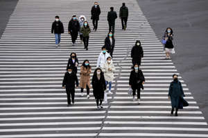 People wearing face masks cross a road as the country is hit by an outbreak of the novel coronavirus, in Shanghai, China March 2, 2020. REUTERS/Aly Song
