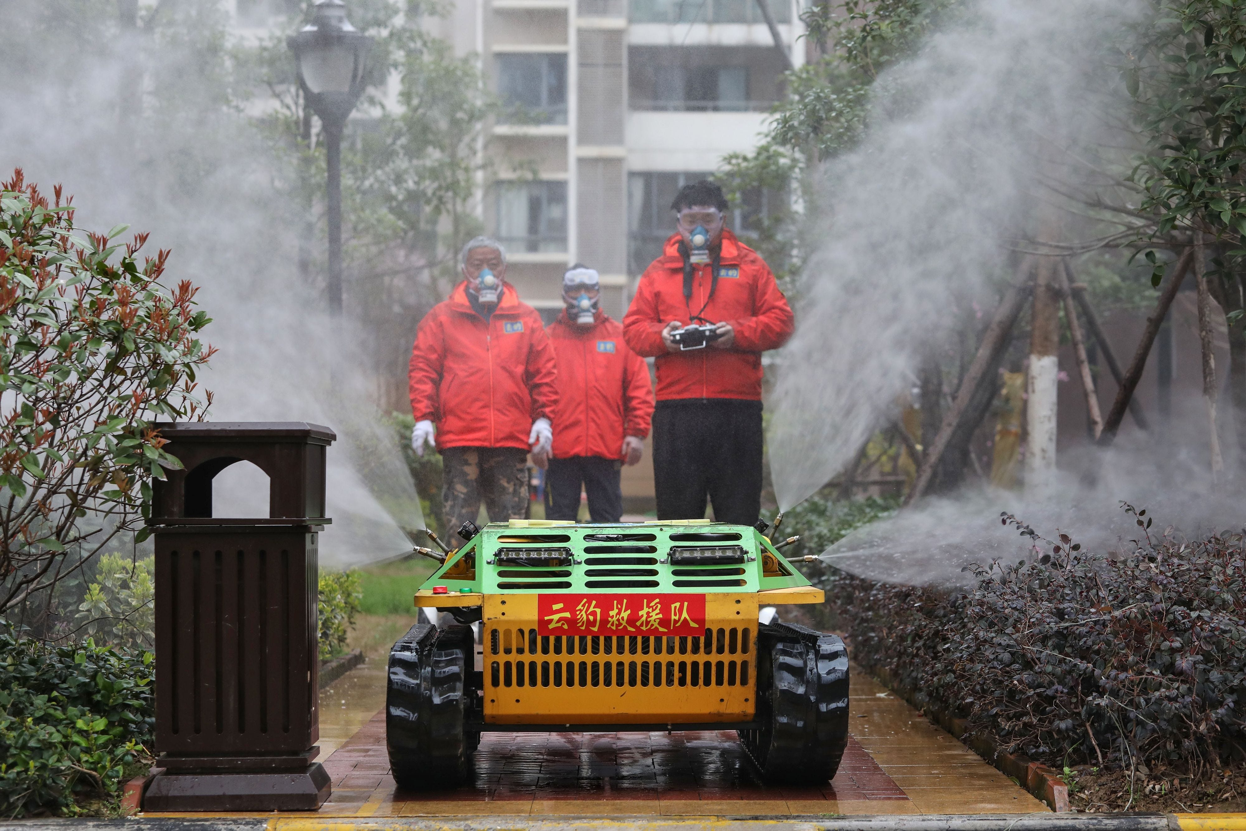 Slide 90 of 113: Volunteers spray disinfectant with a robot at a residental area in Wuhan in China's central Hubei province on March 3, 2020. The world has entered uncharted territory in its battle against the deadly coronavirus, the UN health agency warned, as new infections dropped dramatically in China on March 3 but surged abroad with the US death toll rising to six.