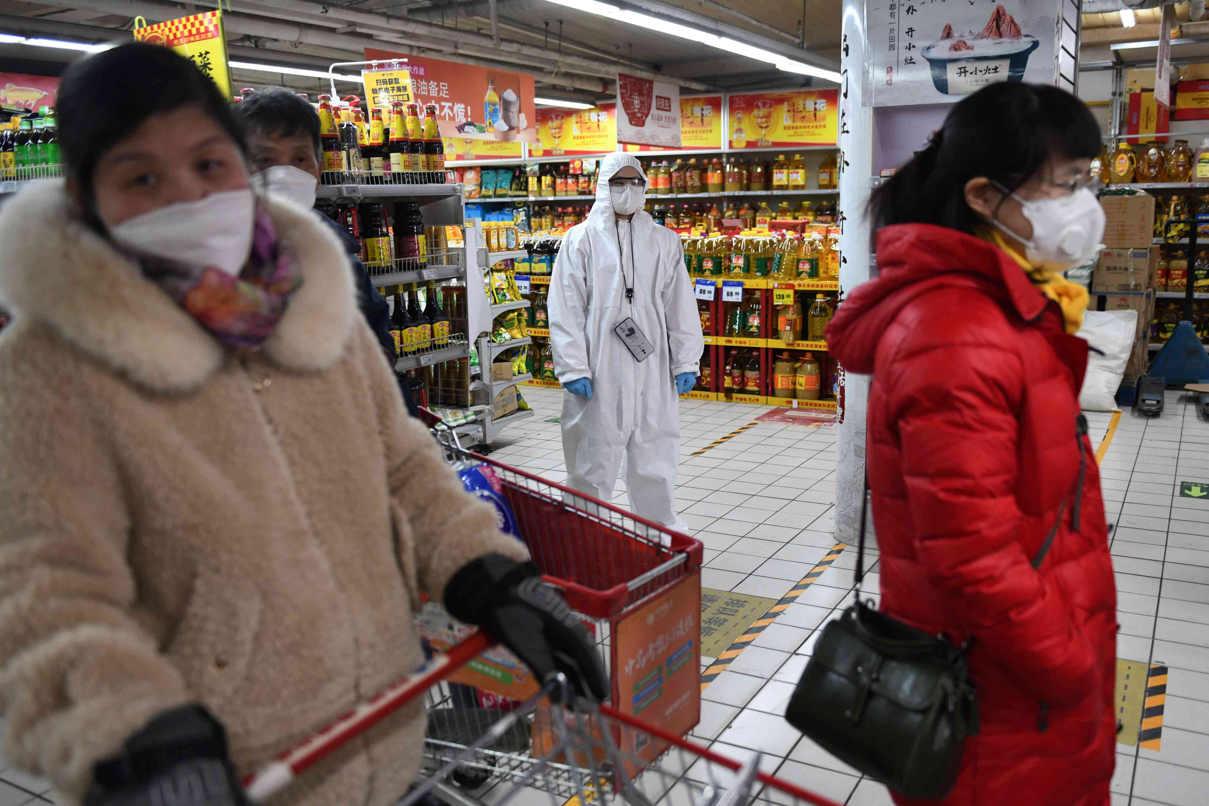 Slide 91 of 113: A worker wears protective clothing as a preventive measure against the COVID-19 coronavirus as she watches over customers in a supermarket in Beijing on March 3, 2020.
