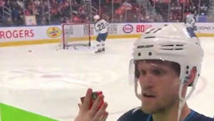 Sweet trade! Hockey player exchanges a puck for candy from a fan