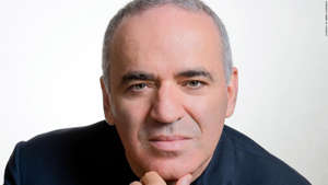 Garry Kasparov wearing glasses and smiling at the camera