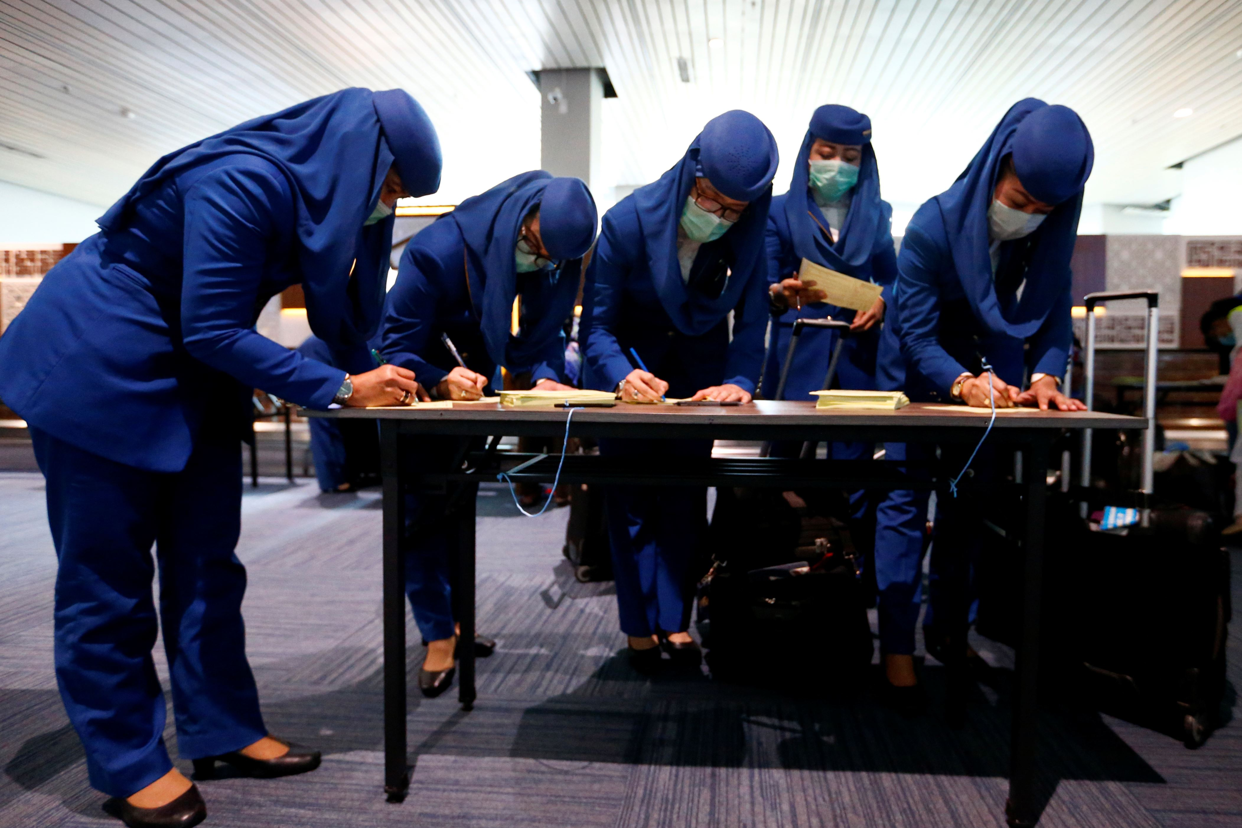 Slide 42 of 55: Flight attendants wearing protective masks fill out health alert cards before thermal scanner checks after Indonesia confirmed its first cases of coronavirus disease (COVID-19), in Soekarno Hatta International Airport, in Tangerang near Jakarta, Indonesia, March 6, 2020. REUTERS/Ajeng Dinar Ulfiana