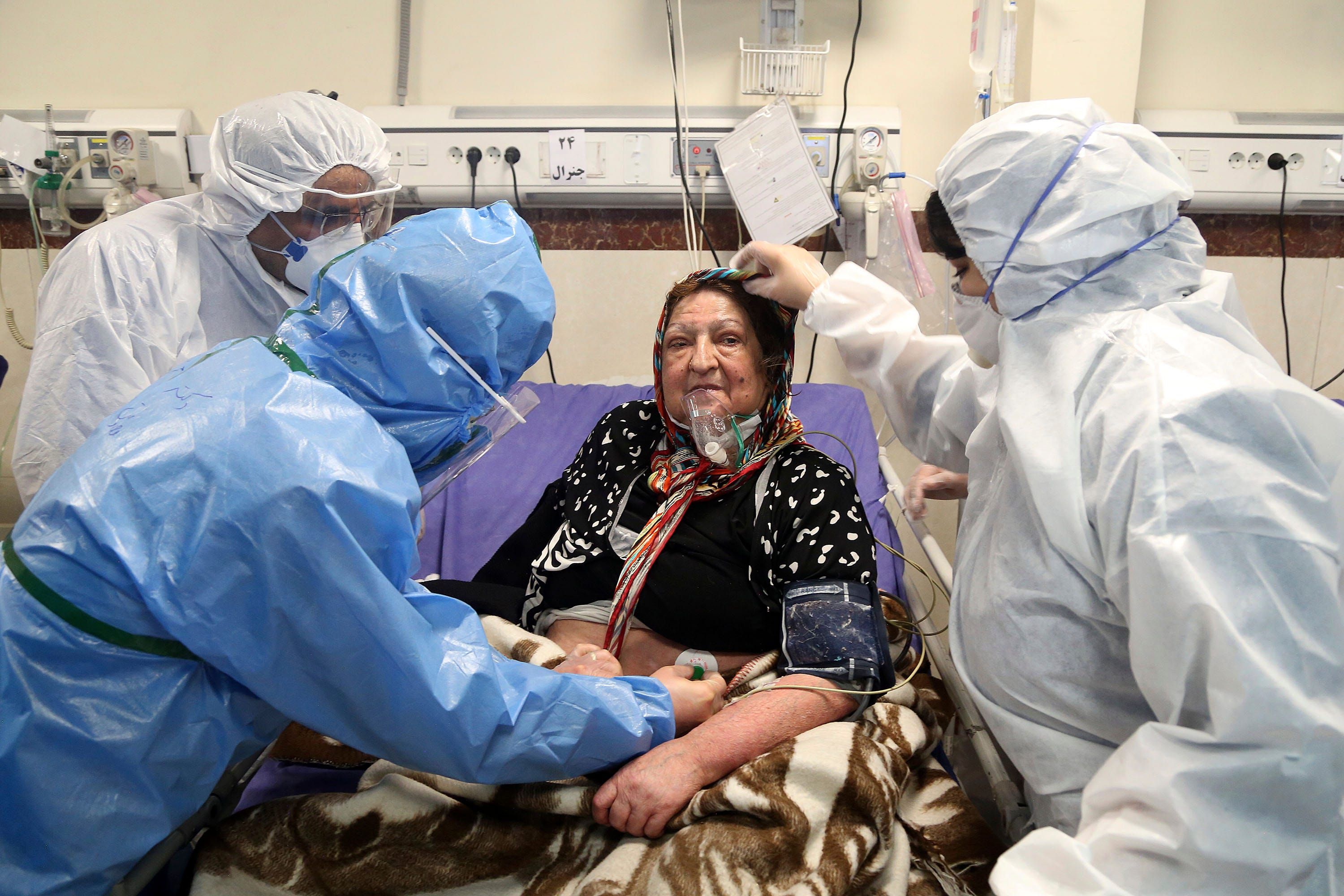 Slide 88 of 113: Medics treat a patient infected with the new coronavirus, at a hospital in Tehran, Iran, Sunday, March 8, 2020. With the approaching Persian New Year, known as Nowruz, officials kept up pressure on people not to travel and to stay home. Health Ministry spokesman Kianoush Jahanpour, who gave Iran's new casualty figures Sunday, reiterated that people should not even attend funerals.