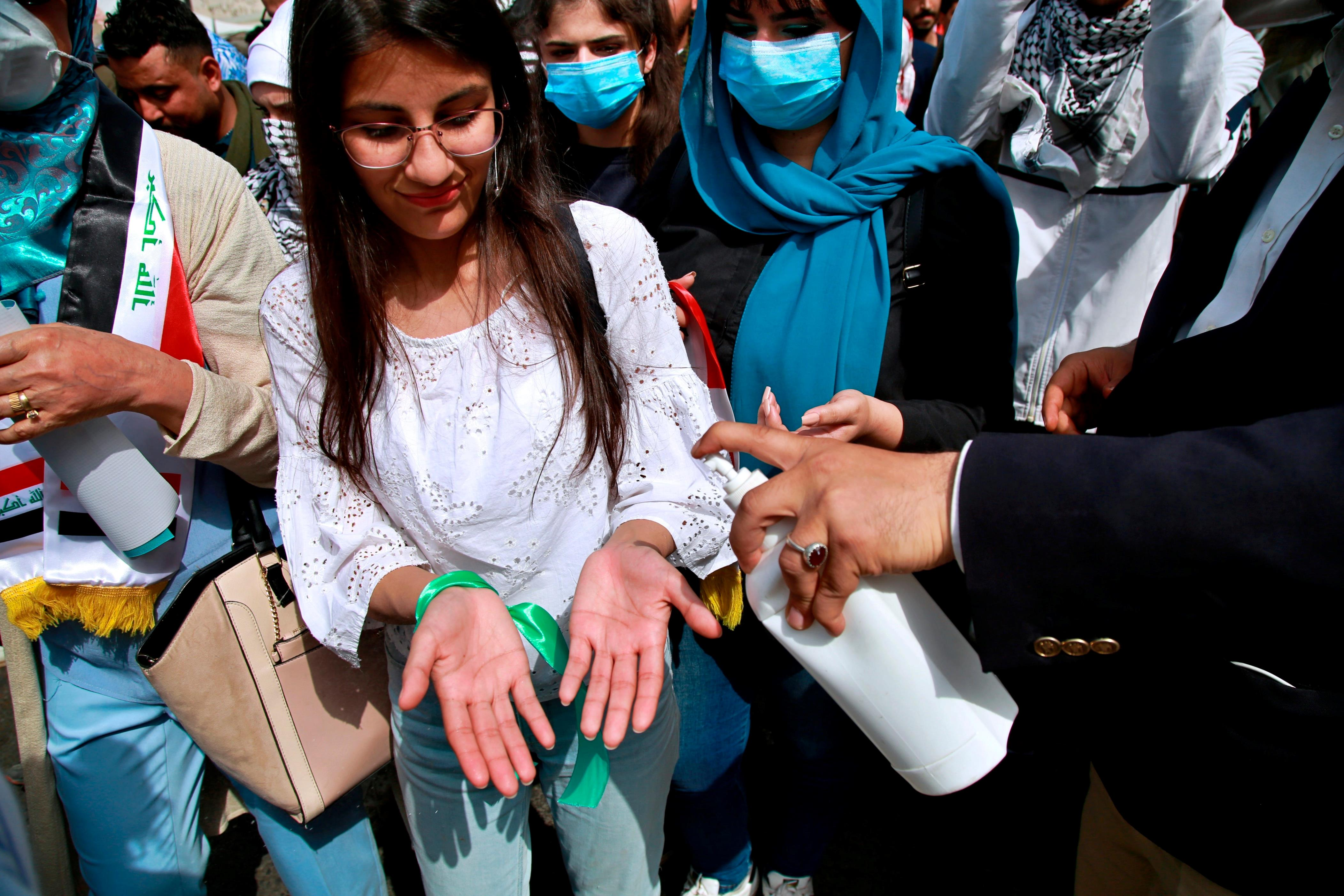 Slide 86 of 113: A protester sprays protesters with sprays disinfectant as a precaution against the coronavirus during a rally demanding women's right during the International Women's Day in Tahrir square in Baghdad, Iraq, Sunday, March 8, 2020.