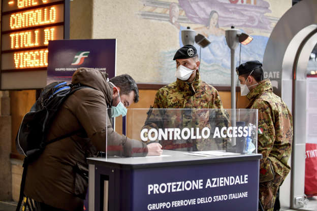 a group of people standing in front of a store: A passenger leaving from Milan Central railway station signs a release form as two soldiers stand by, in Milan, Monday, March 9, 2020. (Claudio Furlan/LaPresse via AP)