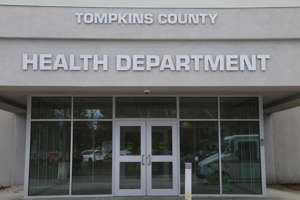 a sign above a store in a brick building: Tompkins County Health Department