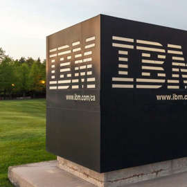Sign of IBM with Canada Head Office Building in background in Markham, Ontario, Canada. IBM is an American multinational technology company.