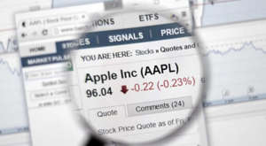 Apple (AAPL) stock information in a magnifying glass.