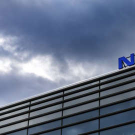 a sign in front of a cloudy blue sky: Dark clouds over Nokia (NOK) brand name on top of a building in Helsinki, Finland