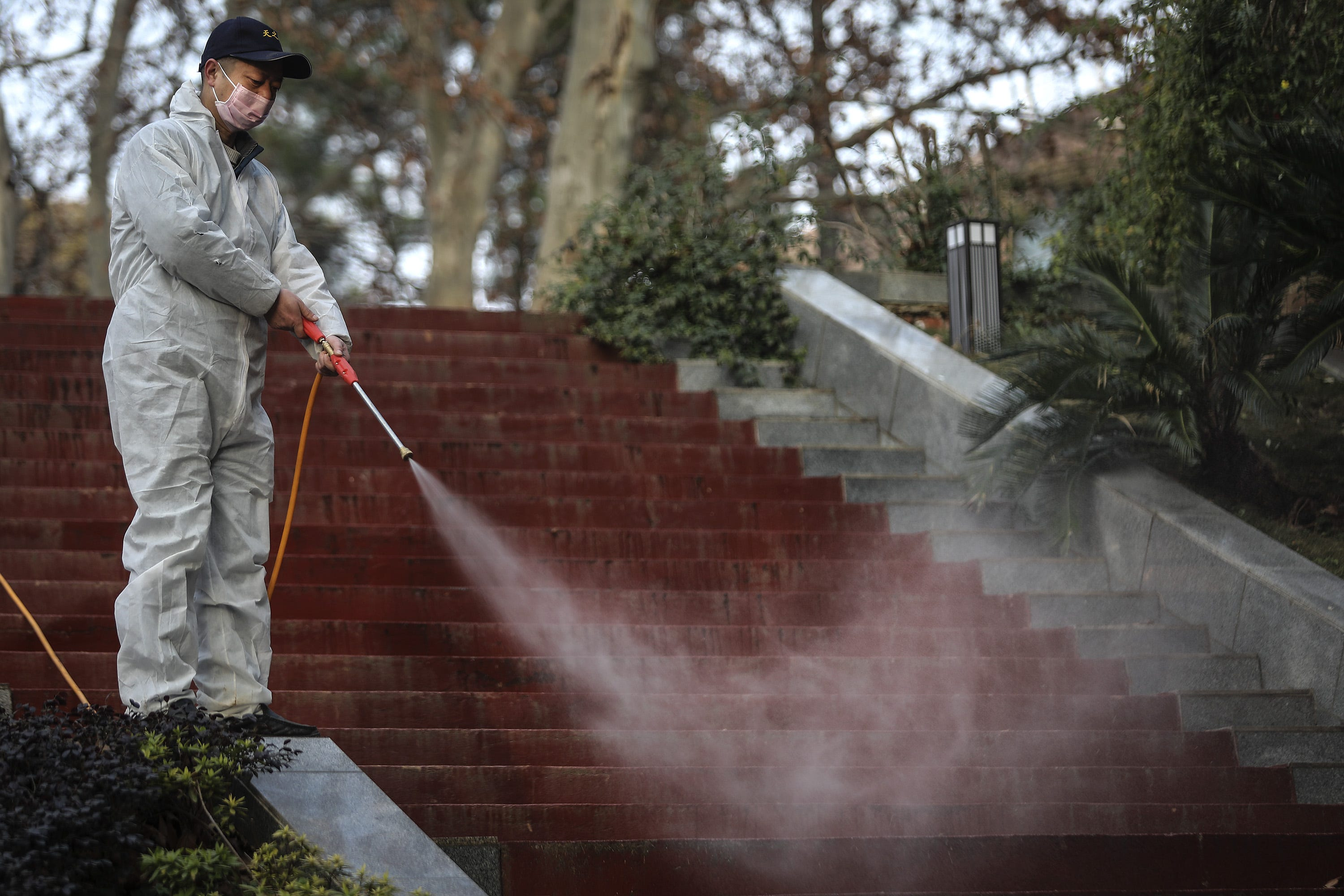 Slide 110 of 113: A man uses alcohol to disinfect the grounds nearby the Wuhan Huoshenshan hospital construction site on Jan. 28, 2020 in Wuhan, China.