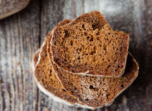 "a close up of a piece of bread: Whole wheat bread likely isn't the health food you were hoping for. Many loaves are packed with high fructose corn syrup and molasses, especially those that are marketed as ""honey whole wheat."" Choose a sprouted bread such as Ezekiel to make sure you're getting added nutrients without added sugar."